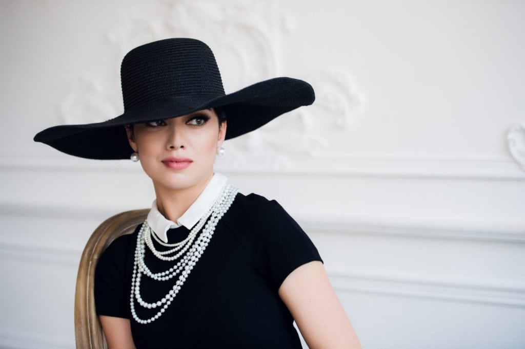 Portrait of a beautiful young woman in retro style in an elegant black hat and dress over luxury rococco wall background.